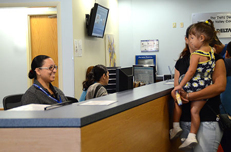 Mother holding her child in a BVCHC office location with a smiling receptionist